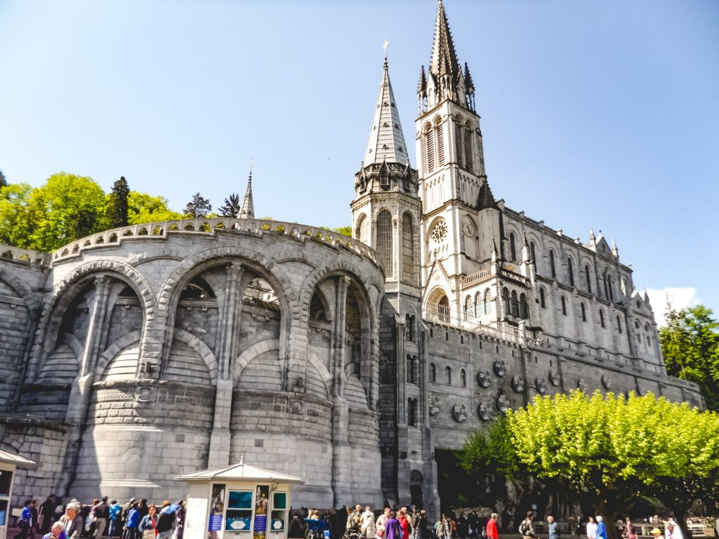 Pilgrims and tourists at The Sanctuary of Our Lady of Lourdes - in Lourdes, France.